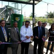 Photo of people at the ribbon cutting for the solar biopower system grand opening.