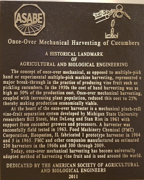 Photo of a historical landmark of Agricultural and Biological Engineering: Once-over mechanical harvesting of cucumbers.   The concept of once-over mechanical, as opposed to multiple-pick hand or experimental multiple-pick machine harvesting, represented a major break-through in the practice of producing vine fruit such as pickling cucumbers.  In the 1950's the cost of hand harvesting was as high as 50% of the production cost.   Once-over mechanical harvesting, coupled with increasing plant population, reduced this cost to 25% thereby making production economically viable.  At the heart of the once-over harvester is a mechanical pinch-roll vine-fruit separation system developed by Michigan State University researchers Bill Stout, Max DeLong and Stan Ries in 1961 with support from cucumber growers and processors.  A harvester was successfully field tested in 1963.   Food Machinery Chemical (FMC) Corporation, Hoopeston, IL fabricated 1 prototype harvester in 1964 and 5 in 1965.  FMC and other companies manufactured an estimated 230 harvesters in the 1960's and 300 through 2009.     Today, once-over mechanical harvesting has become universally adopted method of harvesting vine fruit and is used around the world.   Dedicated by the American Society of Agricultural and Biological Engineers, 2011.