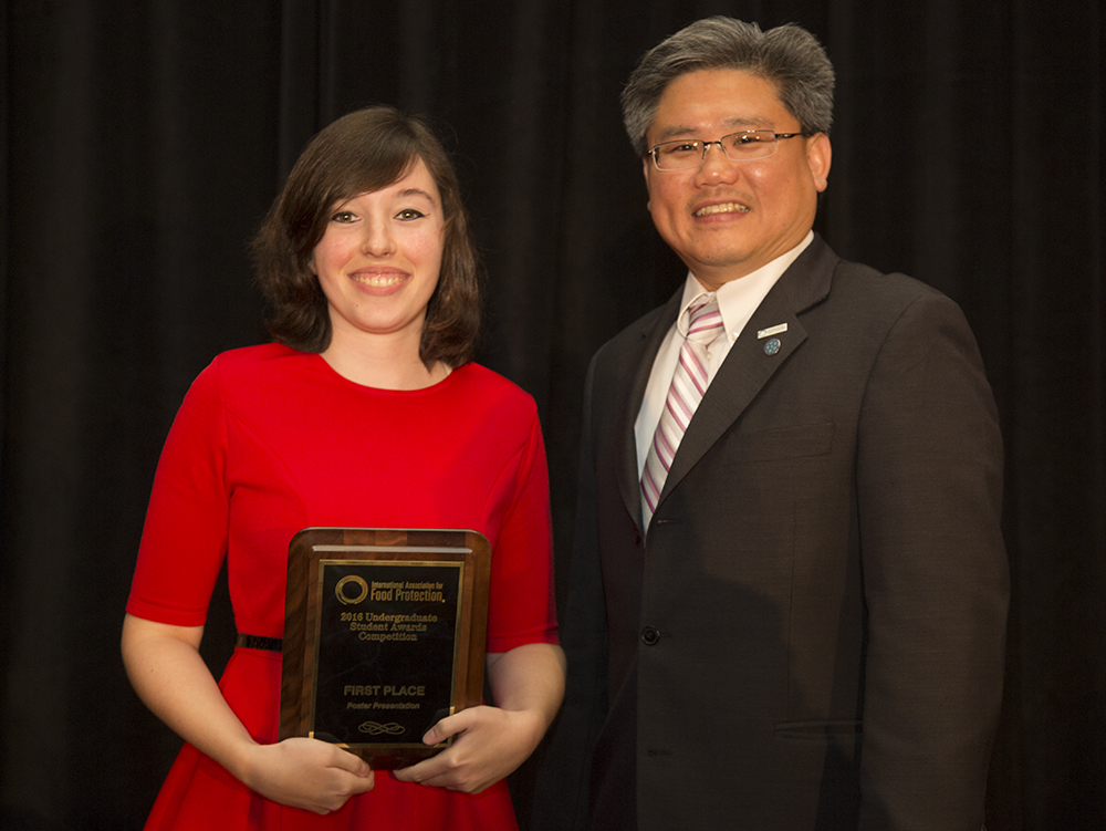 Photo of -	Sarah Buchholz receiving 1st-place in the undergraduate poster competition at IAFP 2016, presented by IAFP Program Chair-Elect, Dr. Alvin Lee.
