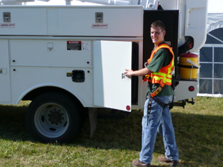 Photo of an apprentice electrician and a work truck