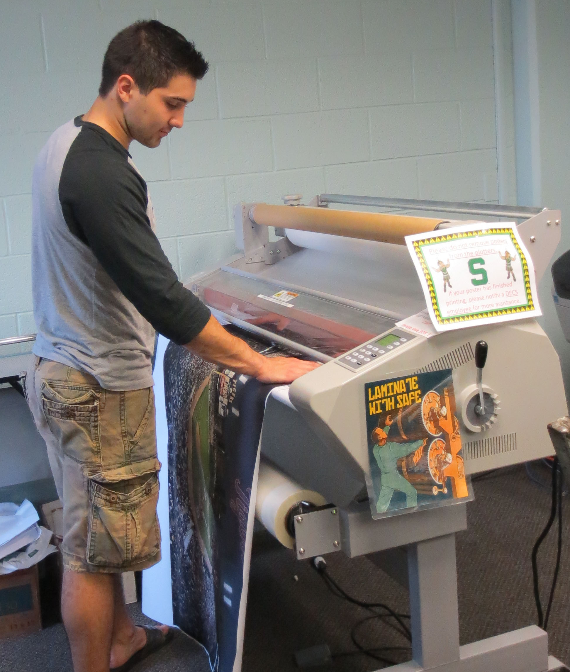 Support office staff laminating a poster