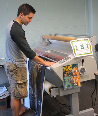 Photo of someone using the DECS laminating machine