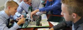 Photo of four boys building robots.