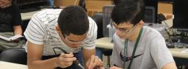 Photo of two students working on a circuit together.