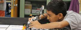 Photo of a young man looking closely at his LEGO robot.