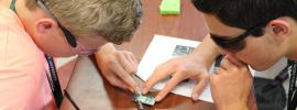 Photo of two young men working on a sodering project in the lab.