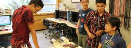 Photo of four students around a table in the lab.