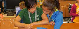 Photo of two young girls working on a LEGO Robot together