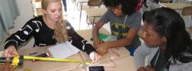 Photo of three high school student campers working on a project together
