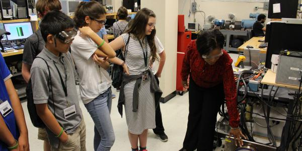 Photo of a group of students in a lab; the instructor is explaining how to use a piece of equipment.