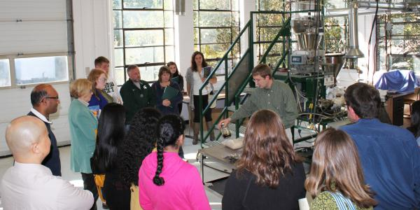 Photo of a group of people visiting the ADREC lab on Preview Day; Professor Christorpher Saffron in center