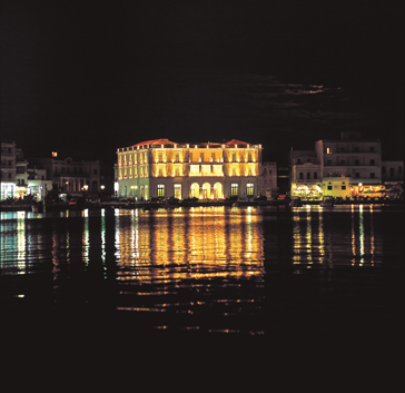 Photo of the Tinos Cultural Foundation at night across the water.