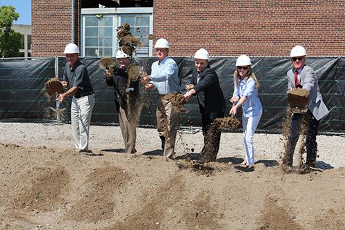 Photo of a ground-breaking event with Engineering faculty holding shovel and tossing dirt