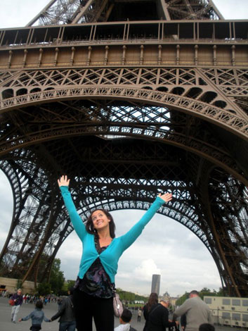 Rachael Dalian standing with her arms in the air in front of the Eifle Tower